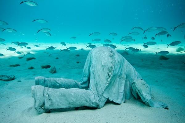 """In apertura, una delle sculture di Jason deCaires Taylor """"Il banchiere"""" circondata da un branco di pesci. In queste pagine, alcune suggestive immagini delle creazioni dello scultore inglese immerse nelle acque di Cancun, in Messico. Previous: The Banker, one of Taylor's"""