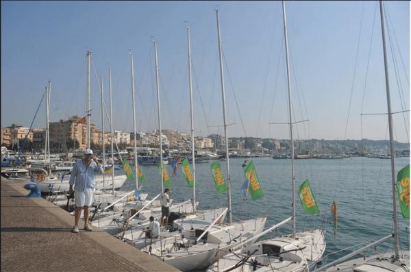 Andrea Cafà sul porto di Anzio con le imbarcazioni iscritte alla regata
