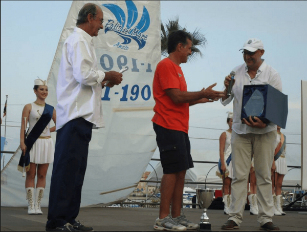 Andrea Cafà delegato da Rita Ajmone Cat consegna il premio al vincitore 1° Classificato, Gianni Riccobono con l'imbarcazione ENJOY.