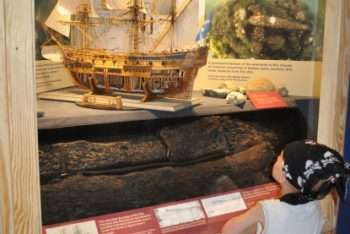 Pirate boy looks at ship model