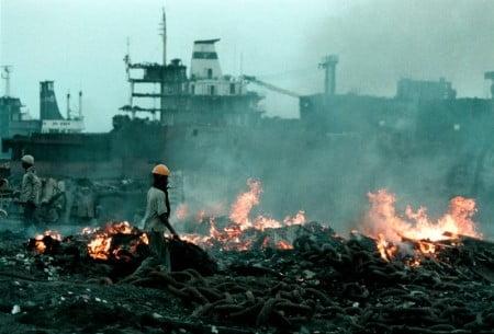 Workers scrapping ship at Alang scrap yard. Gujarat, India